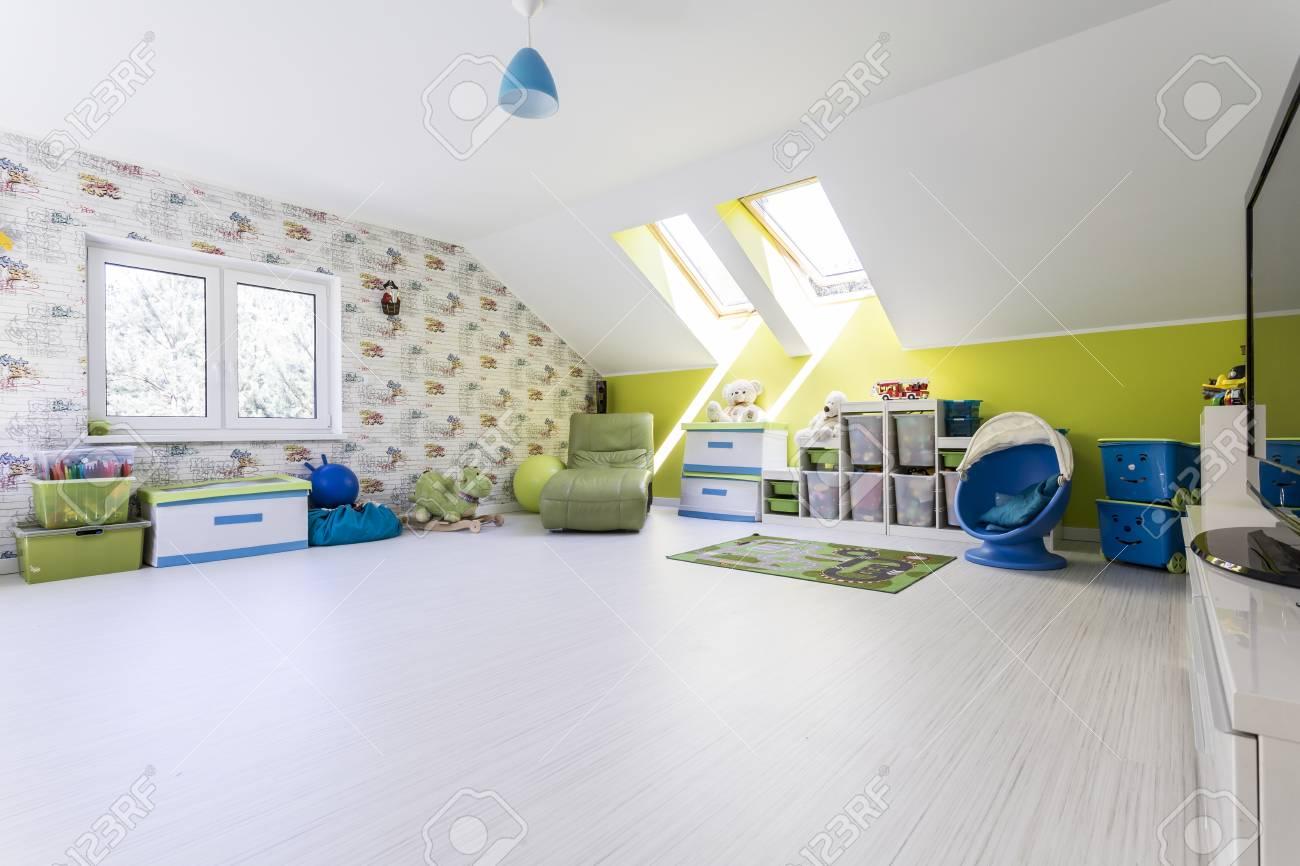 Grande chambre d\'enfant au grenier avec une chaise, une télévision et des  boîtes pour les jouets