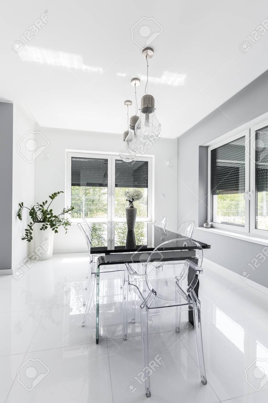 Comedor minimalista moderno diseñado en blanco con mesa negra y sillas  transparentes