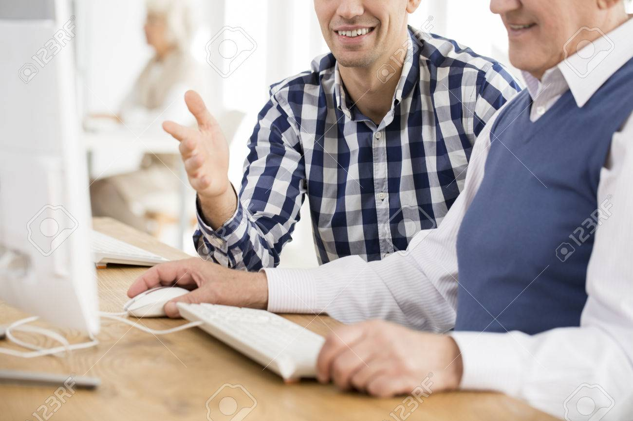 Young lecturer helping older man with computer task - 81575751