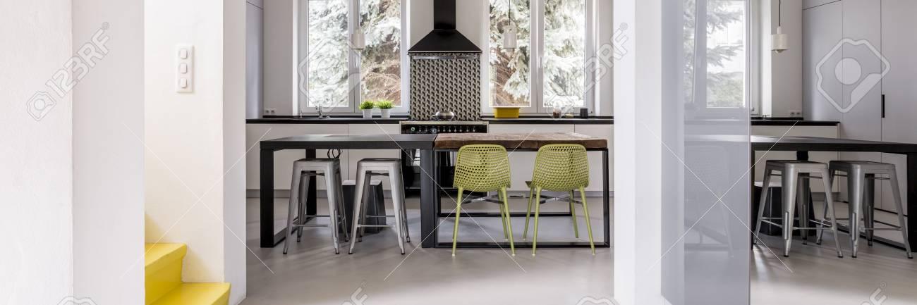 Vista de la escalera con escaleras amarillas y cocina moderna con mesas de  comedor