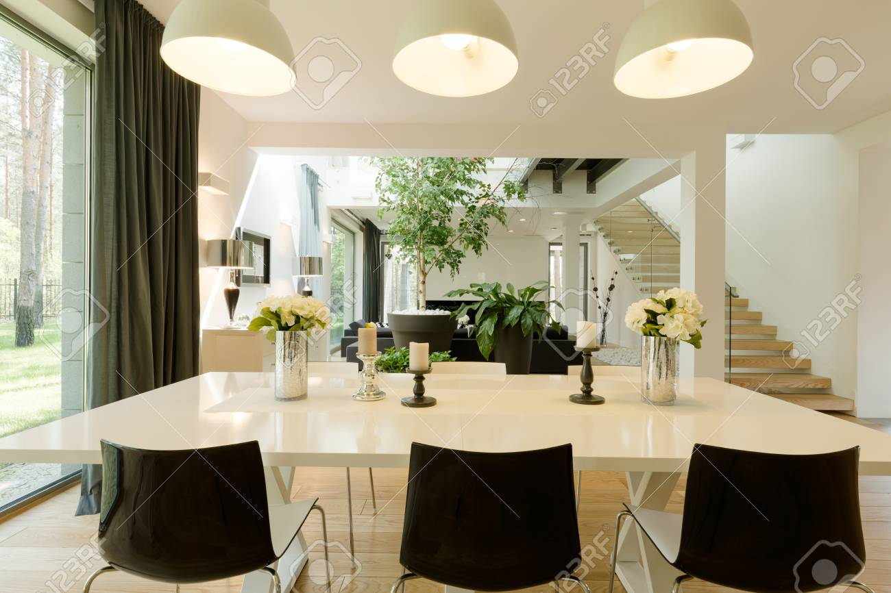 Modern dining room witch a big table, minimalistic chairs and..