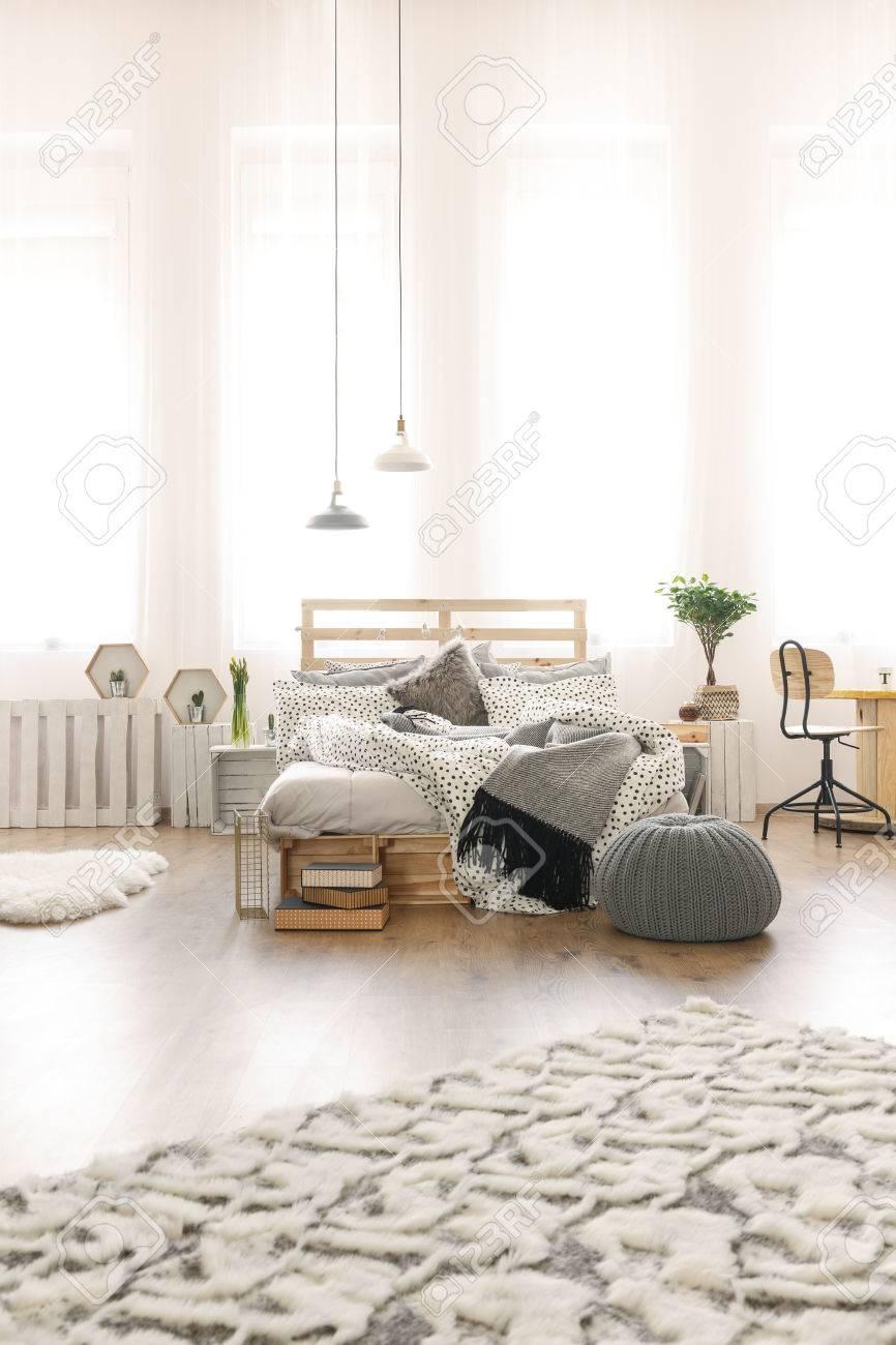 Chambre lumineuse avec lit de palette de bricolage, lampe, moquette de  modèle