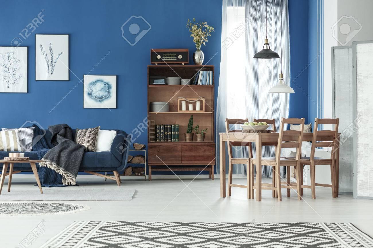 Elegante apartamento clásico con mesa de comedor de madera y sofá vintage