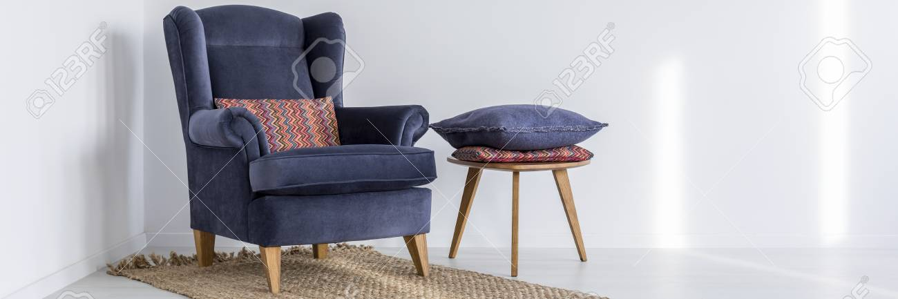 Navy Armchair On A Rug And Wooden Stool With Pillows In White Room Stock  Photo