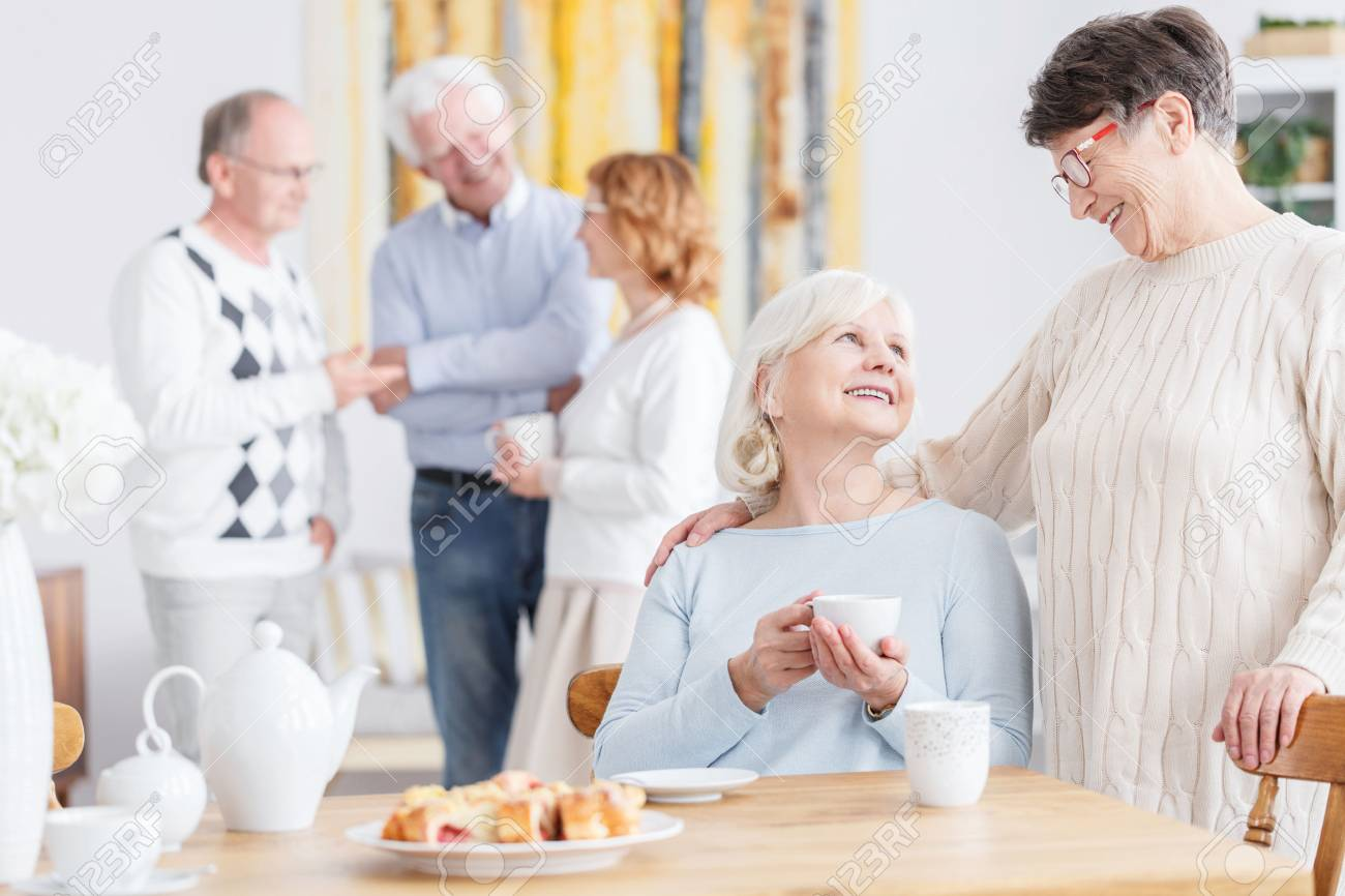 Elderly friends on a tea party at neighbor's home - 81873547
