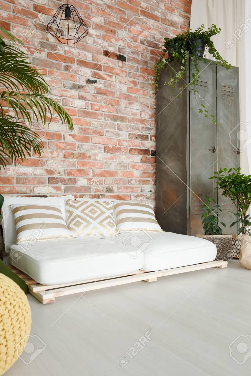 Canapé blanc confortable par le mur de brique rouge dans une chambre  spacieuse
