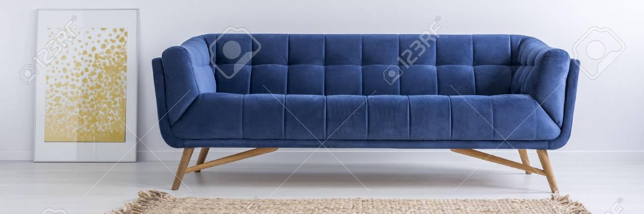 Affiche jaune, canapé bleu et tapis marron dans une chambre moderne