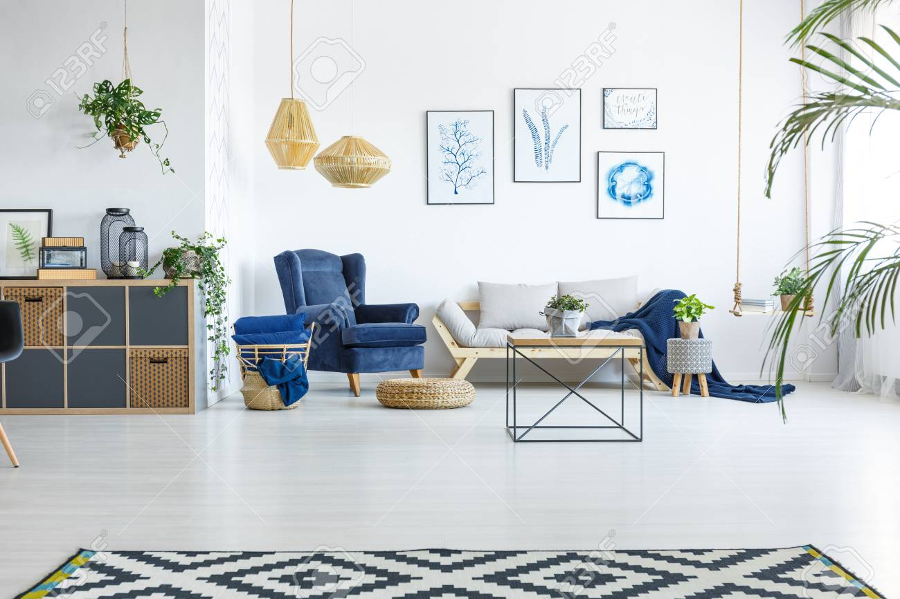 Spacious living room with sofa, armchair and posters - 82160755