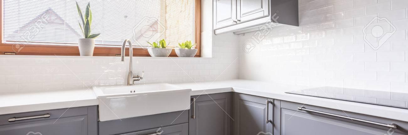 Cucina bianca e grigia con grande finestra di legno sul muro