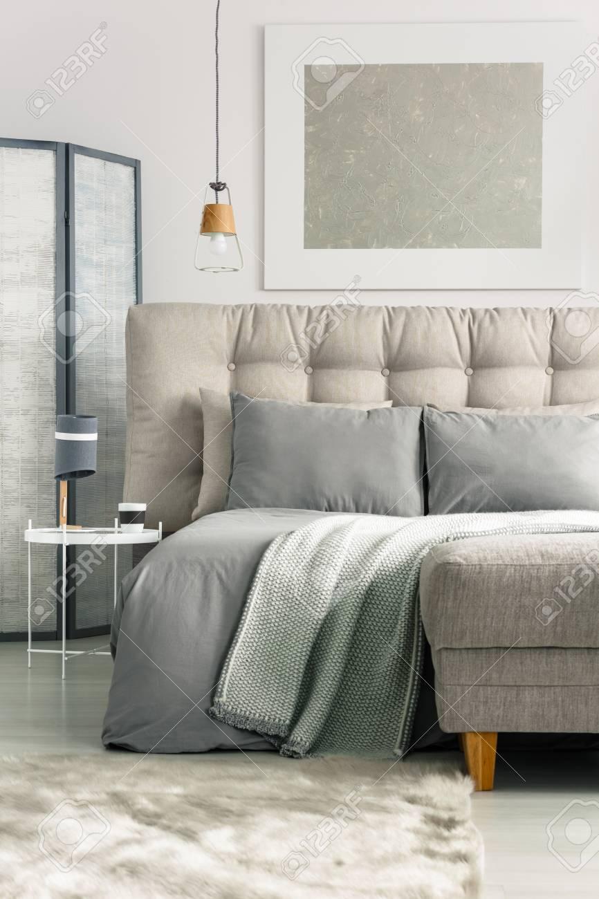 Graues Gemütliches Schlafzimmer Mit Bequemem Bett Und Ottomane  Standard Bild   82081740