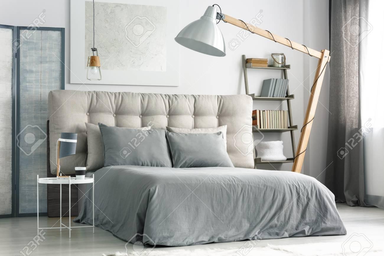 Große Holzlampe In Der Nähe Von Bequemen Bett Mit Grauen Betten