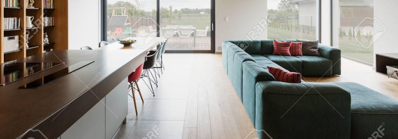 Geräumiges Wohnzimmer Mit Holzboden Verbunden Mit Speisesaal Und Küche  Verbunden. Im Hintergrund Große Fenster Mit