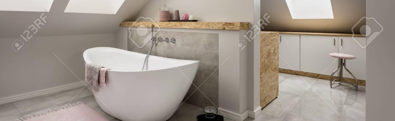 Badezimmer Im Dachgeschoss Mit Einer Ovalen Badewanne Und Weiter Zum  Hauswirtschaftsraum Mit Schränken Standard Bild