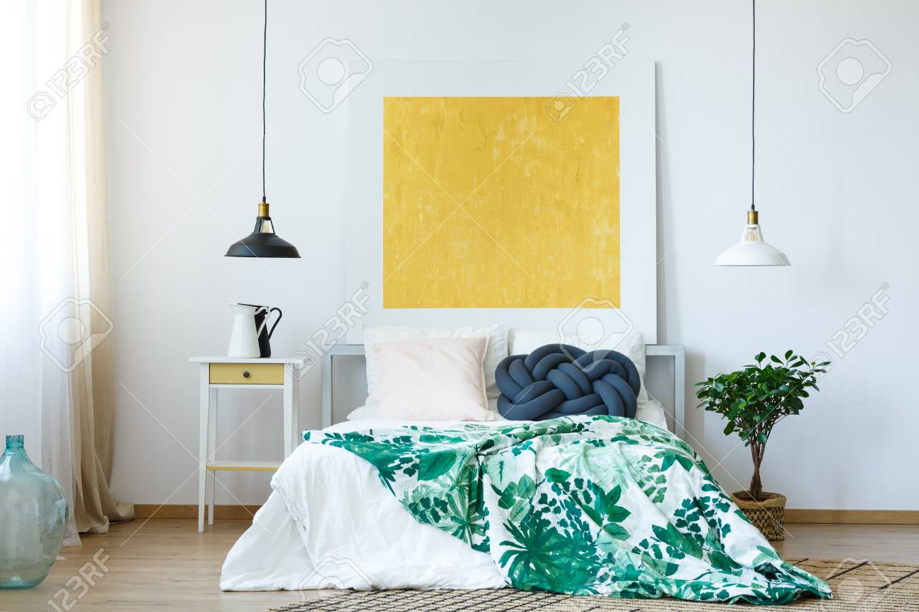 Yellow abstract painting in bright, stylish bedroom