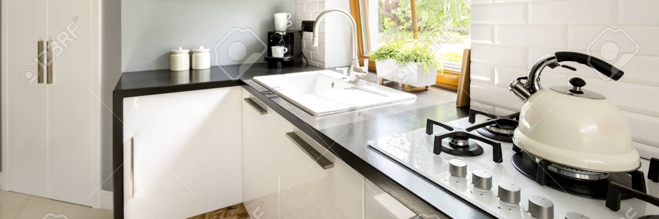 clear and simple kitchen with gas burners on which stands the traditional kettle stock photo