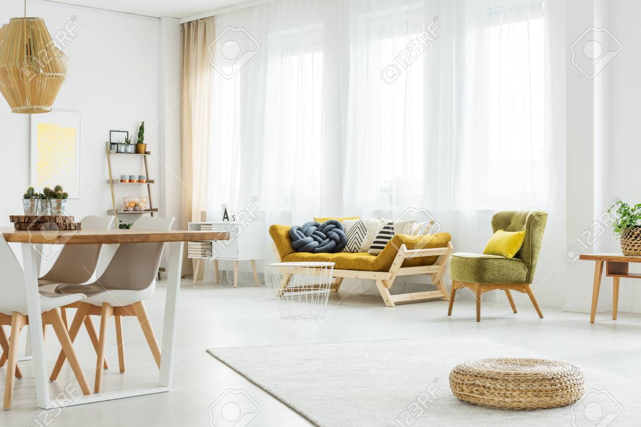 Wooden Mustard Couch And Green Chair In Cozy Living Room Stock Photo ...