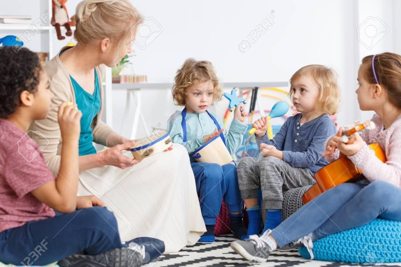 Niños Pequeños En El Jardín De Infantes Jugando Instrumentos Durante ...
