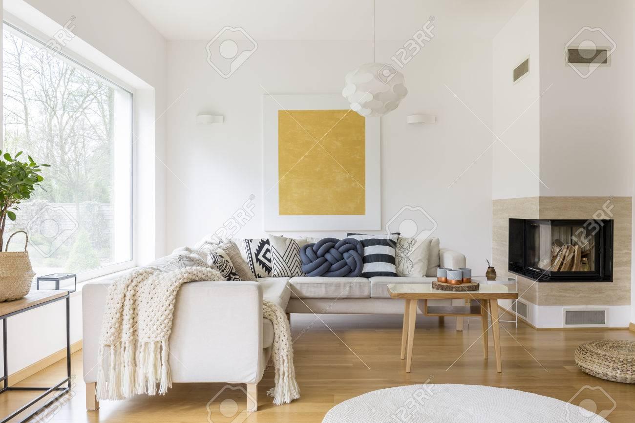 Canapé blanc avec des oreillers et cheminée moderne dans le salon élégant