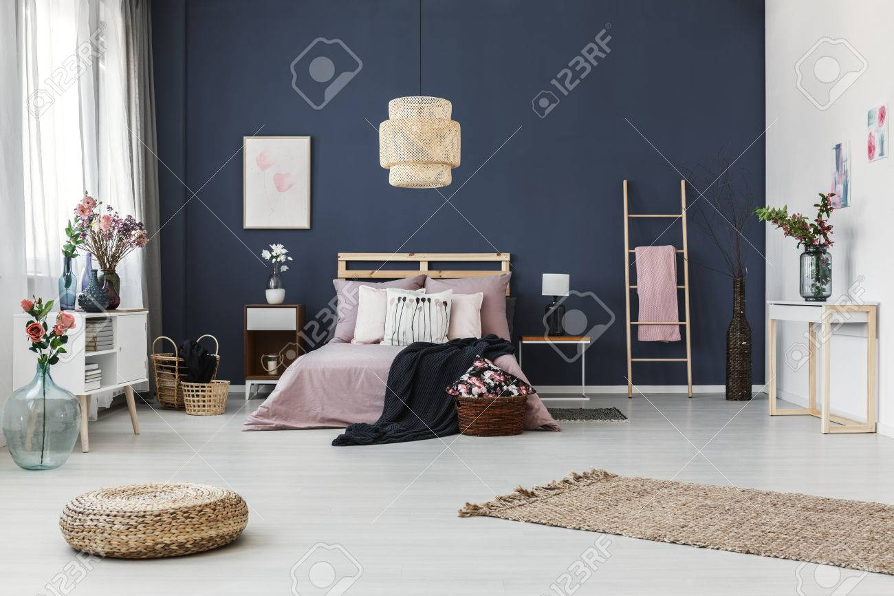 Painting hanging on dark blue wall in cozy bedroom with fresh..