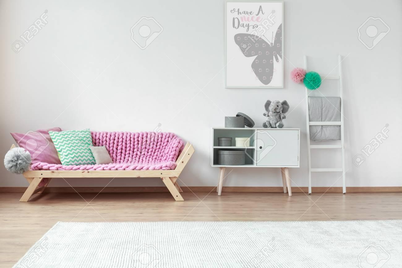Coussins colorés allongé sur un canapé en bois rose dans la chambre  d\'enfant avec affiche