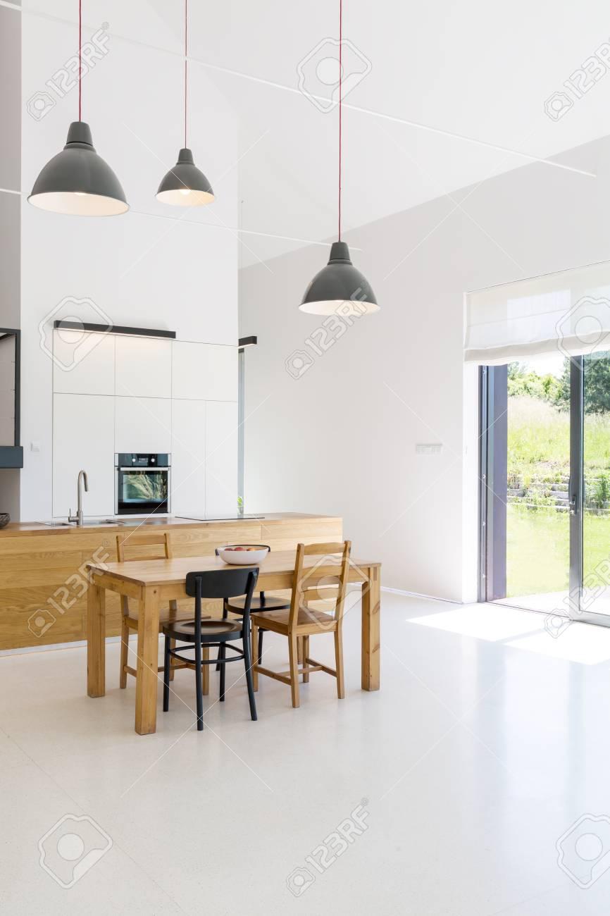 Intérieur spacieux d\'une cuisine et salle à manger dans une maison  contemporaine, murs blancs, sol et plafond