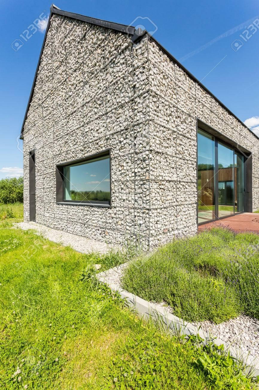 Maison moderne en pierre de galets avec de grandes fenêtres, entourée  d\'herbe sauvage