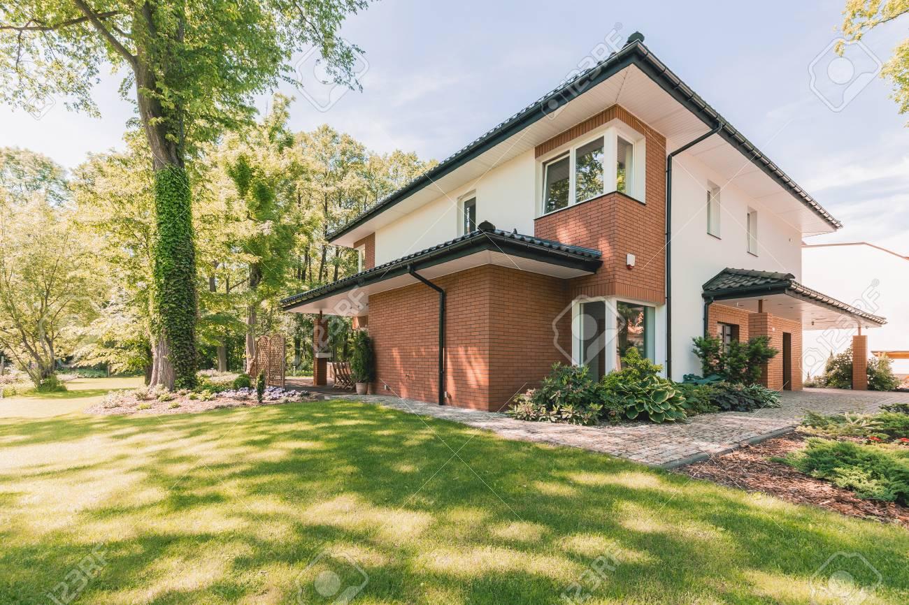 Buitenkant van privé zomerhuis met terras en zonnige tuin royalty