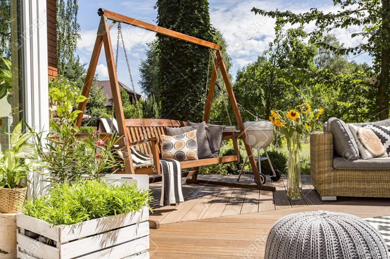 Shot Of A Wooden Garden Swing In A House Terrace Full Of Plants