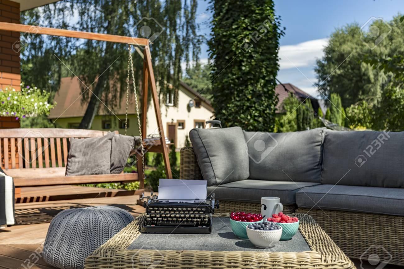 Véranda d\'une maison avec mobilier de jardin, balançoire en bois et machine  à écrire sur une table basse