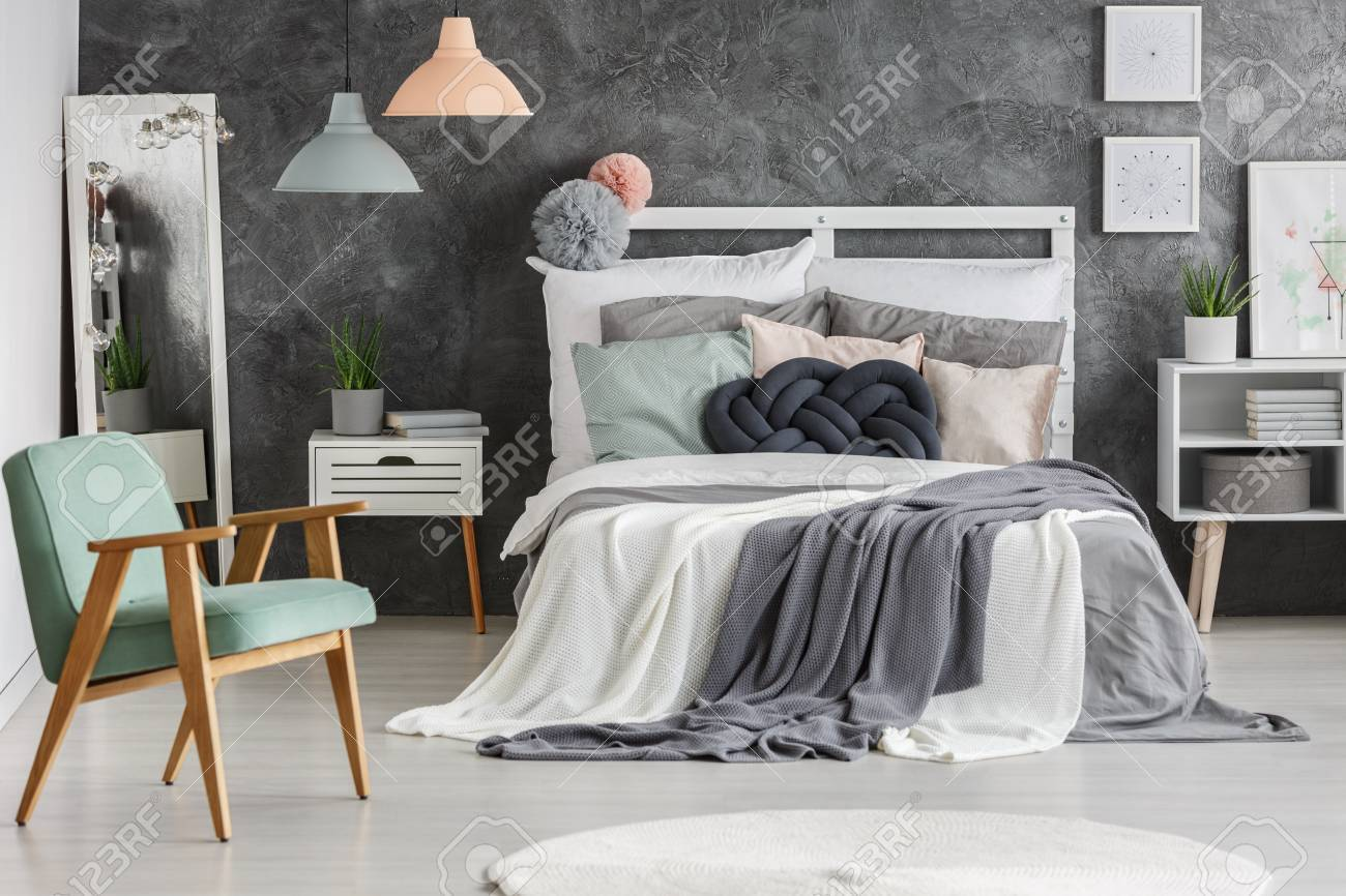 White Wooden Bed With Messy Blankets In Cozy Teen Girls Room Stock