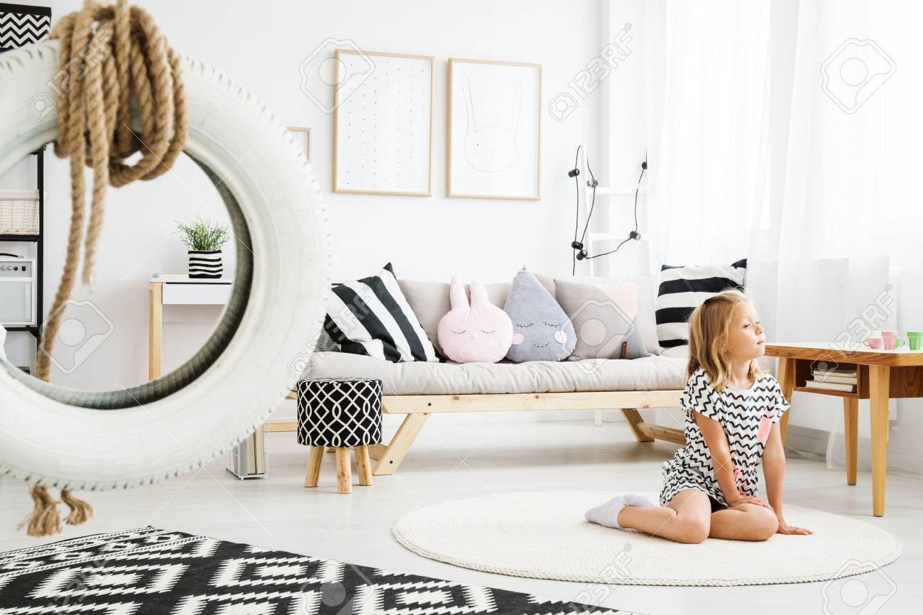 Petite fille blonde assise sur le sol dans une chambre blanche à la mode en  Scandinavie