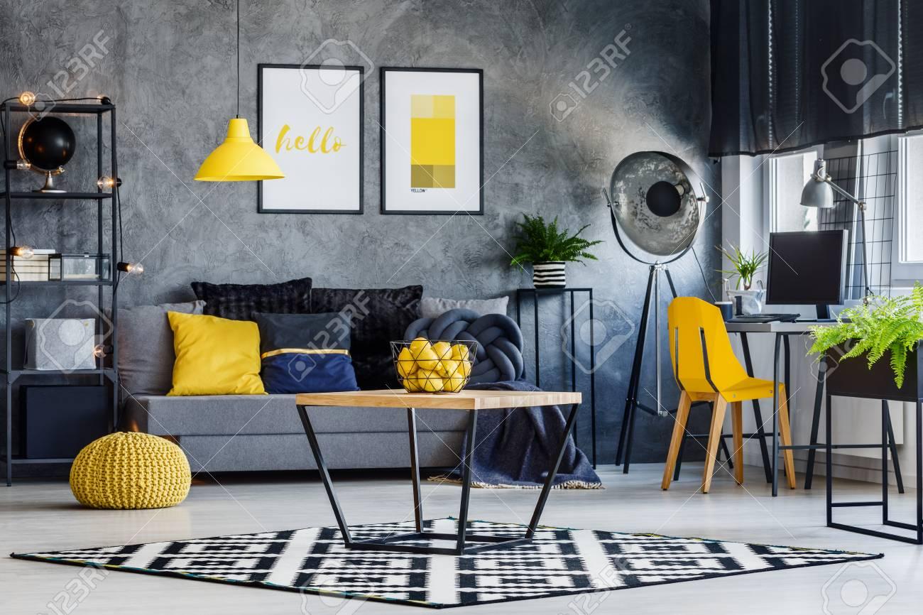 Décor de chambre masculine avec lampe jaune, chaise, pouf, affiche et  coussins