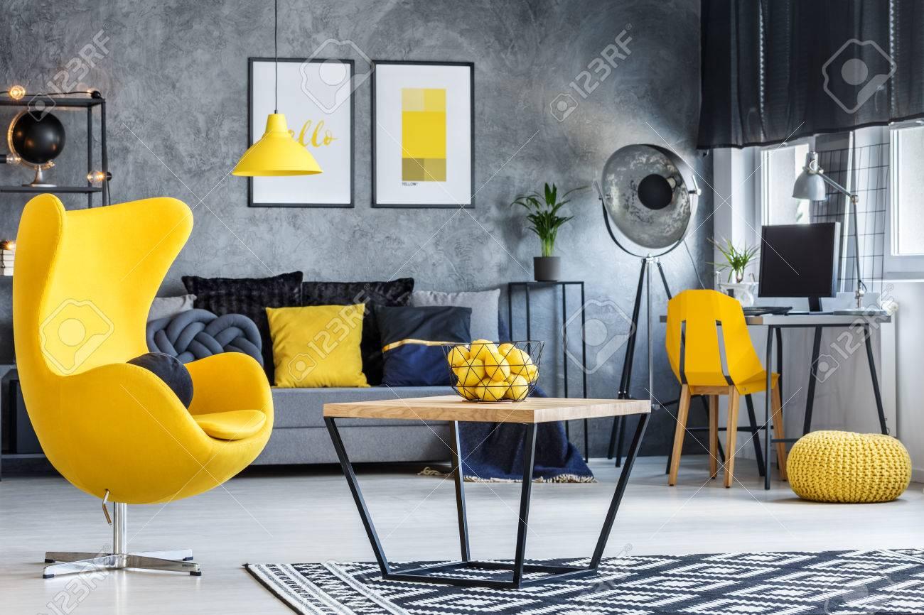 Chambre hipster avec table basse, fauteuil design jaune et murs en béton