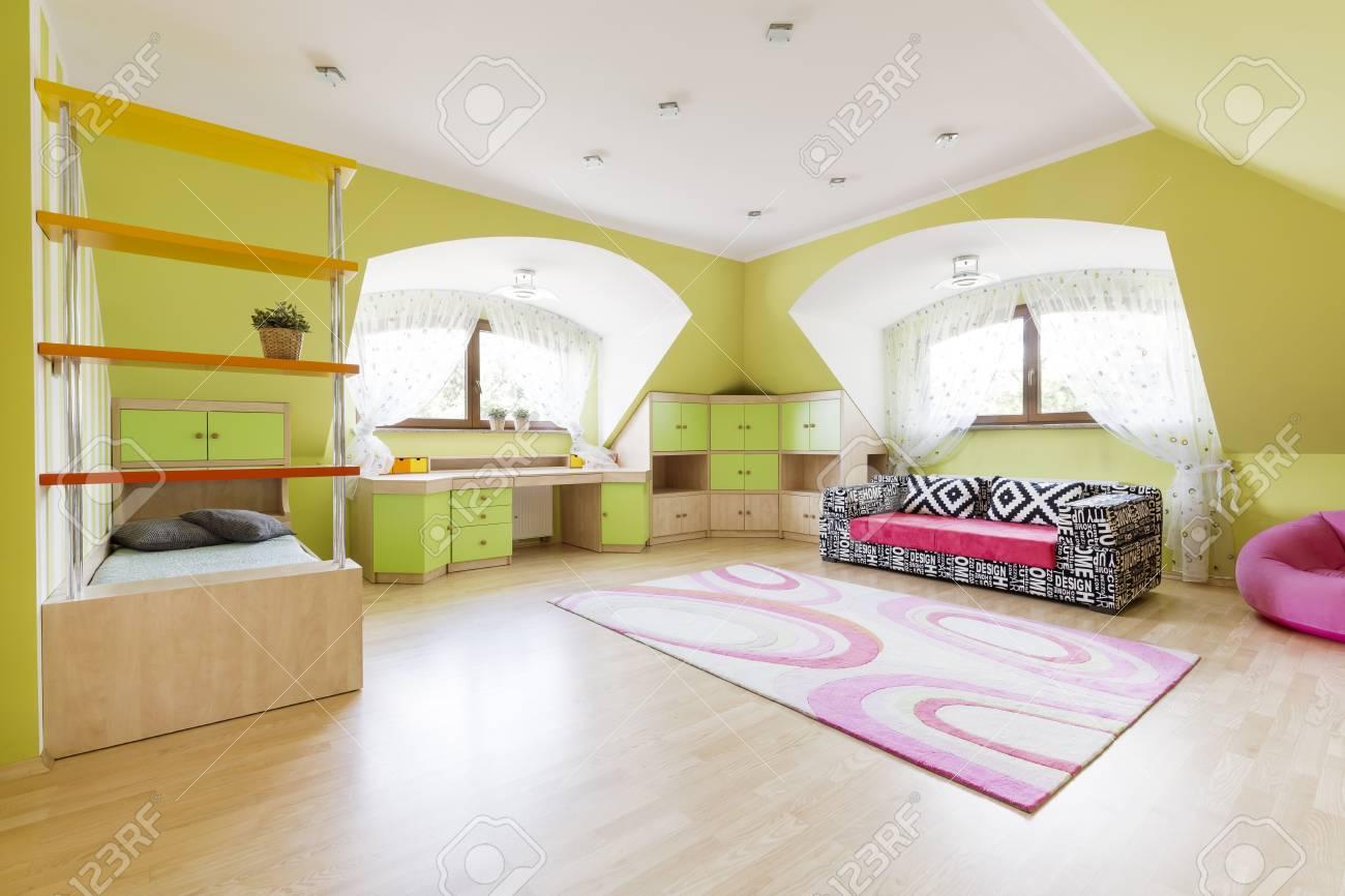 Ampia camera da letto per bambini con divano alla moda vicino al muro e  moquette rosa su un parquet in legno