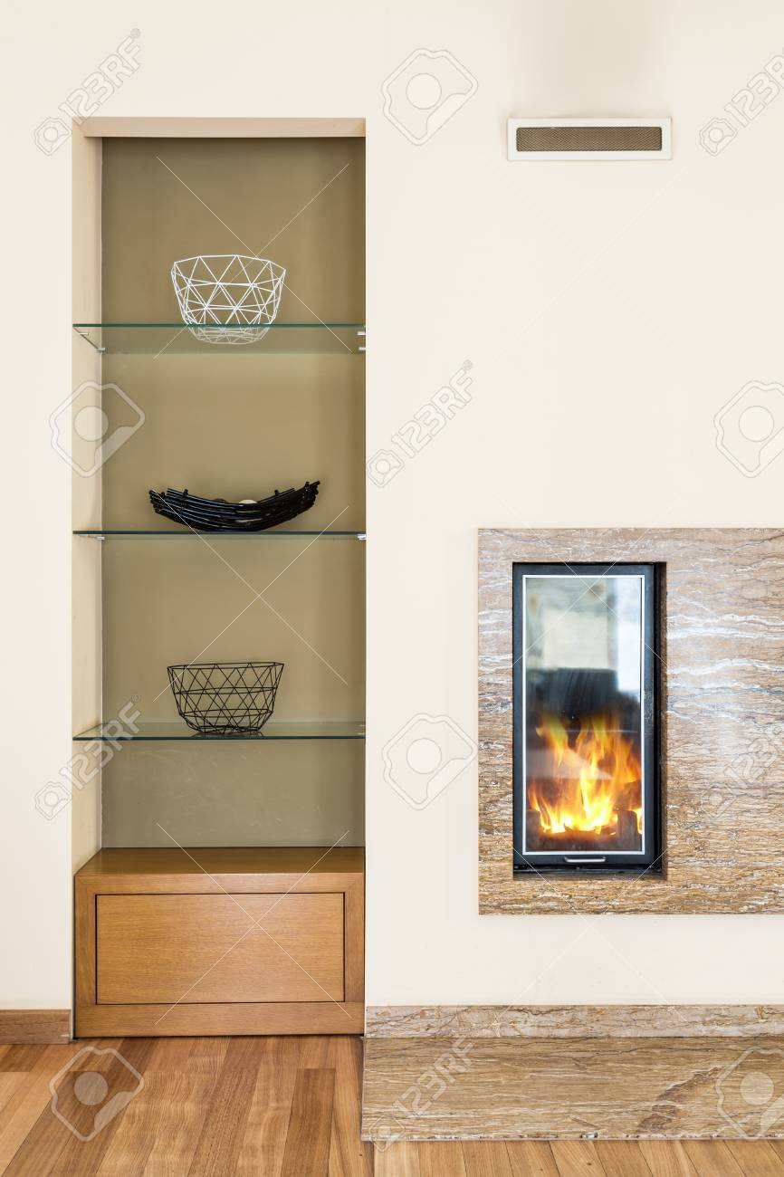 Salon moderne avec élégante cheminée élégante. Sur la gauche étagère design  contemporain avec décoration