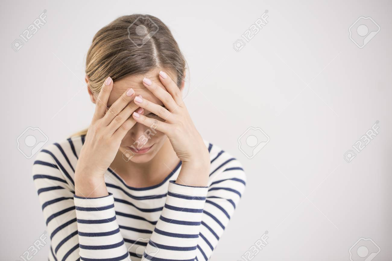 Young hopeless woman suffering from depression having nervous breakdown holding her head on isolated background, copy space - 83654044