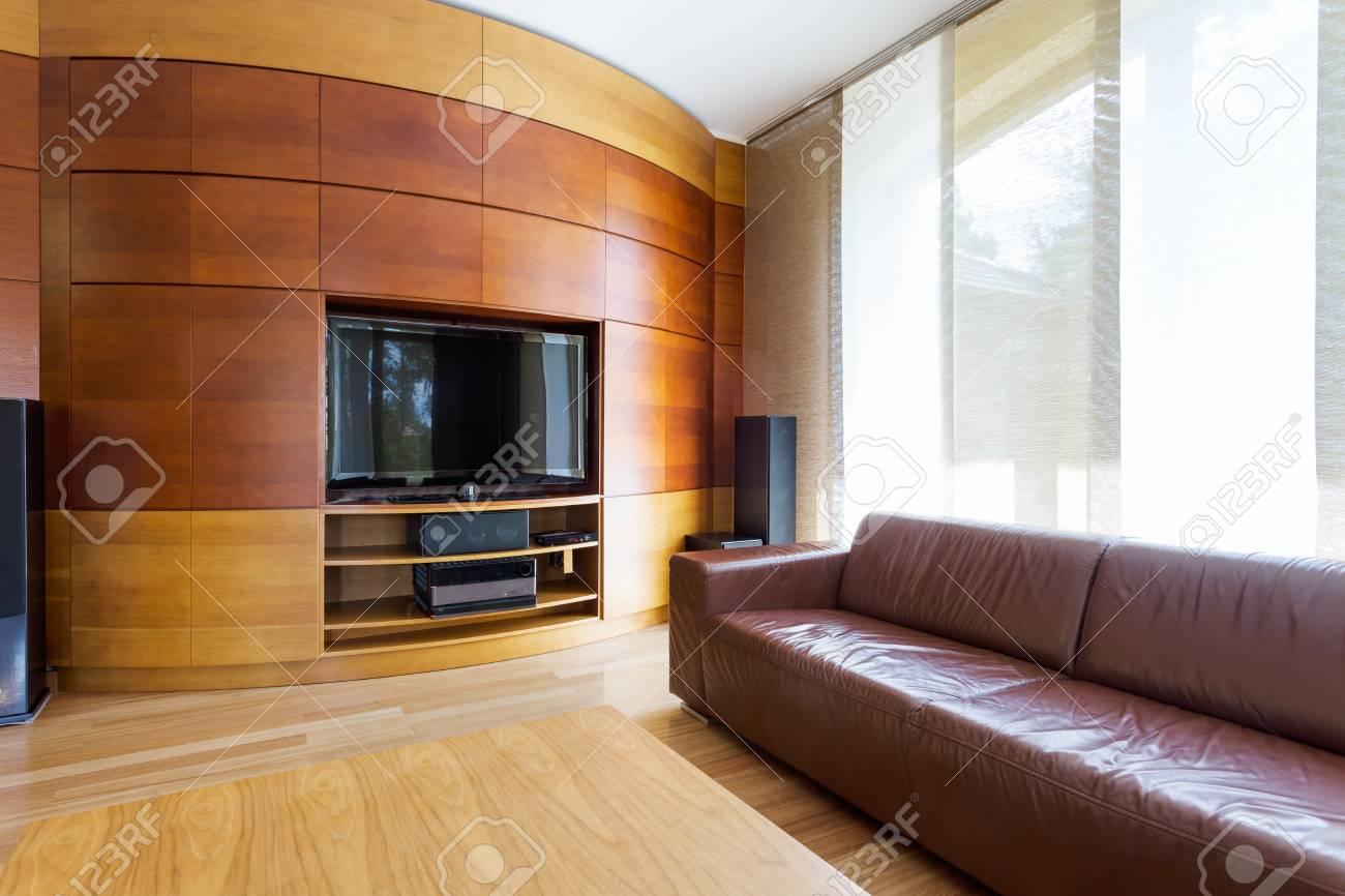 Grand salon moderne dans une riche villa. Canapé en cuir et table basse en  bois à côté du panneau en bois avec télévision