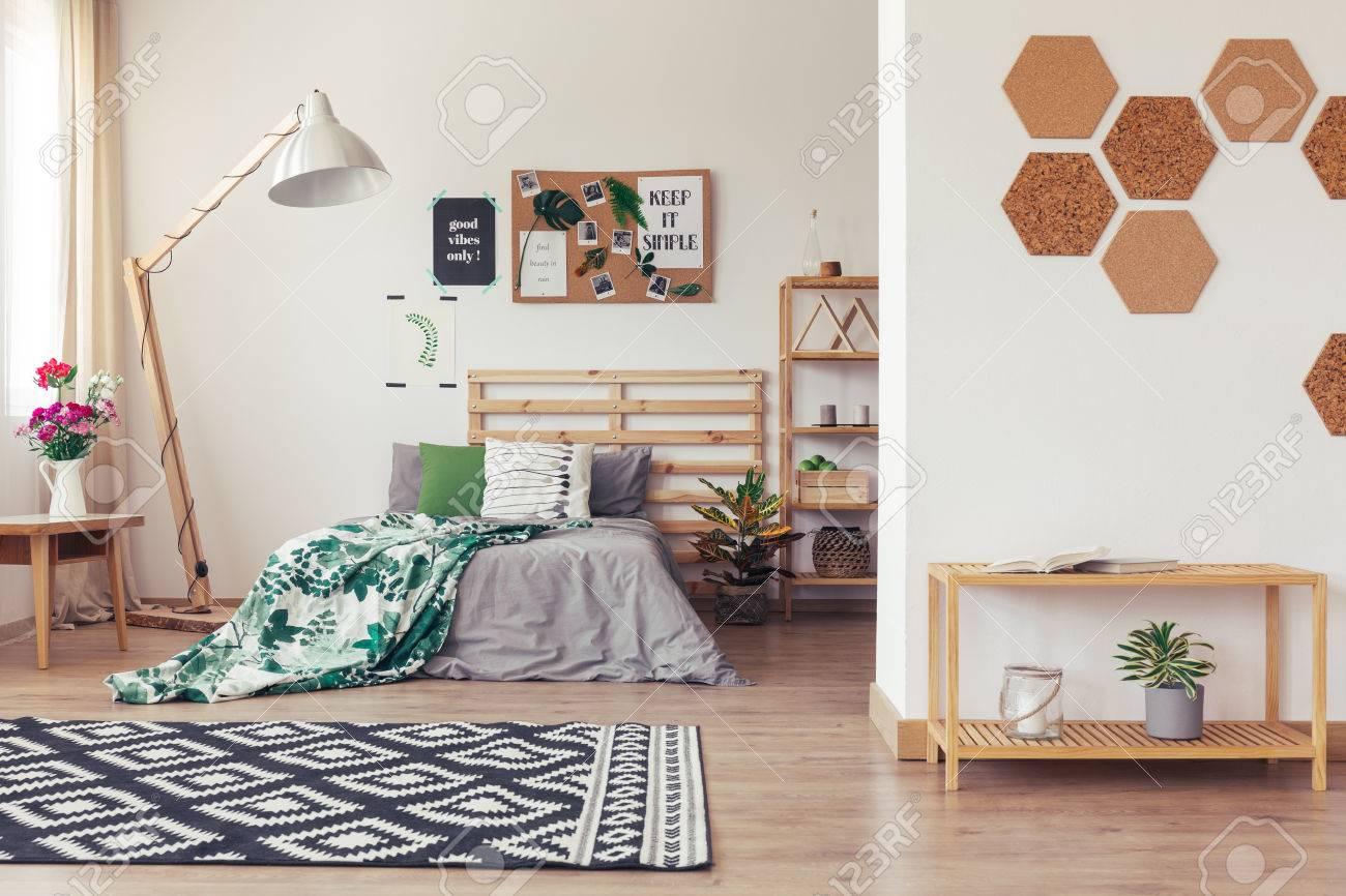 Chambre branchée dans un style écologique avec un décor naturel, literie  grise et verte, support, tapis, vase, fleurs, accessoires en liège et  meubles ...