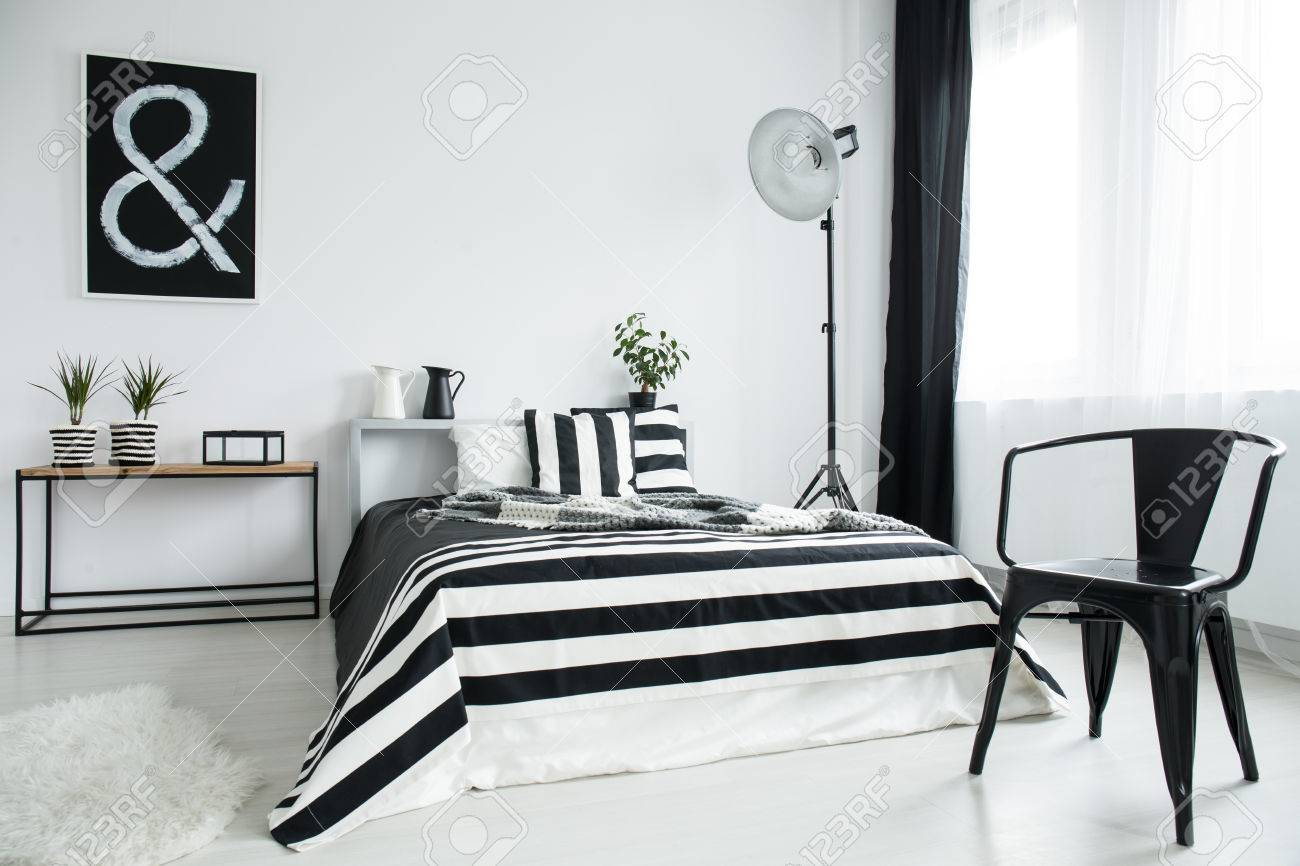 Designed black chair in front of king-size bed with striped coverlet..