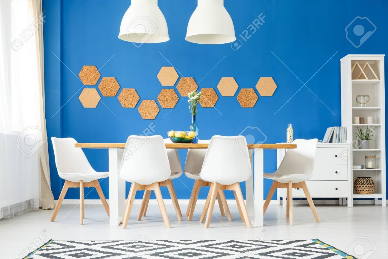banque dimages lgante salle manger moderne avec mur bleu royal table en bois chaises design blanches lampes tapis et mur de lige en nid dabeille