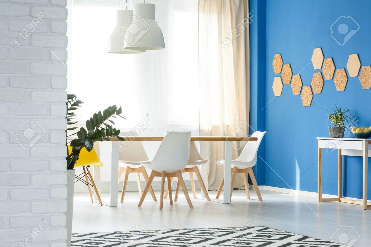 Sillas de madera blancas modernas en el diseño interior del comedor con  decoración natural, pared azul, mesa, sillas, lámparas y gran ventana ...