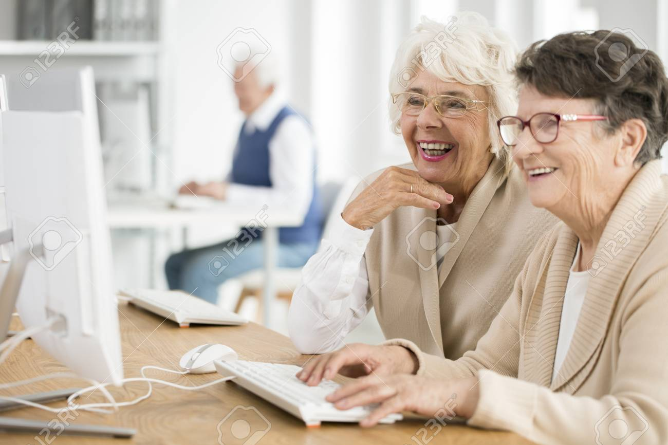Two elder women with glasses learning how to use computer together - 84606456