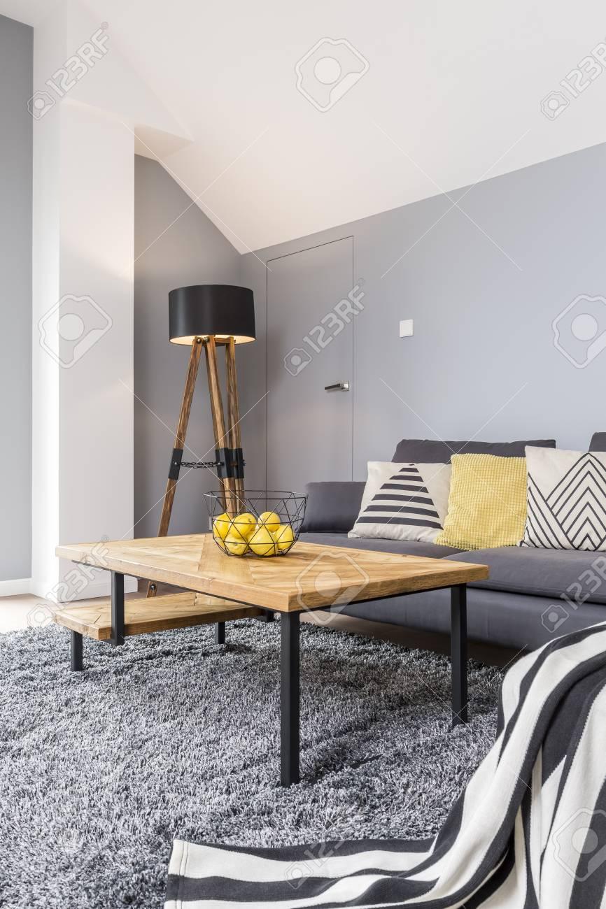 Tapis Et Canapé D Angle design en bois et gris du salon moderne confortable avec canapé d'angle,  couverture à rayures, tapis et table basse design