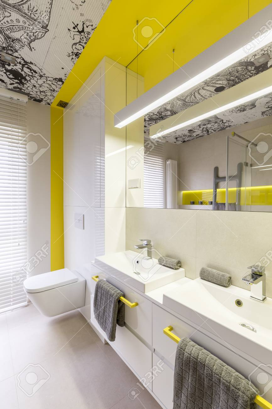 Idée de design de salle de bains blanche et jaune néon, poignées jaunes,  double vasque, toilettes, plafond graphique et fenêtre