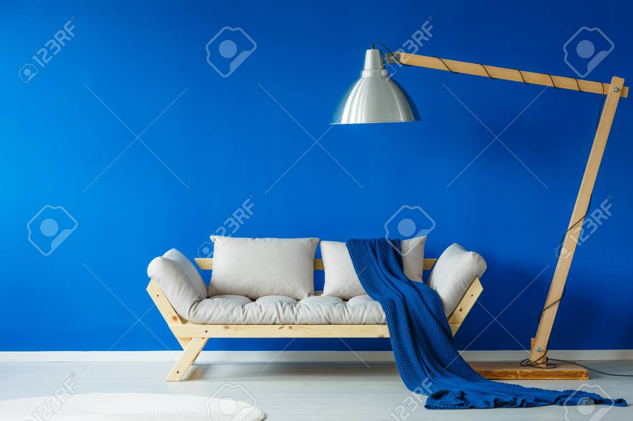 Blue Patterned Blanket Lying On Modern Sofa Next To A Giant Lamp Stock  Photo   84011181
