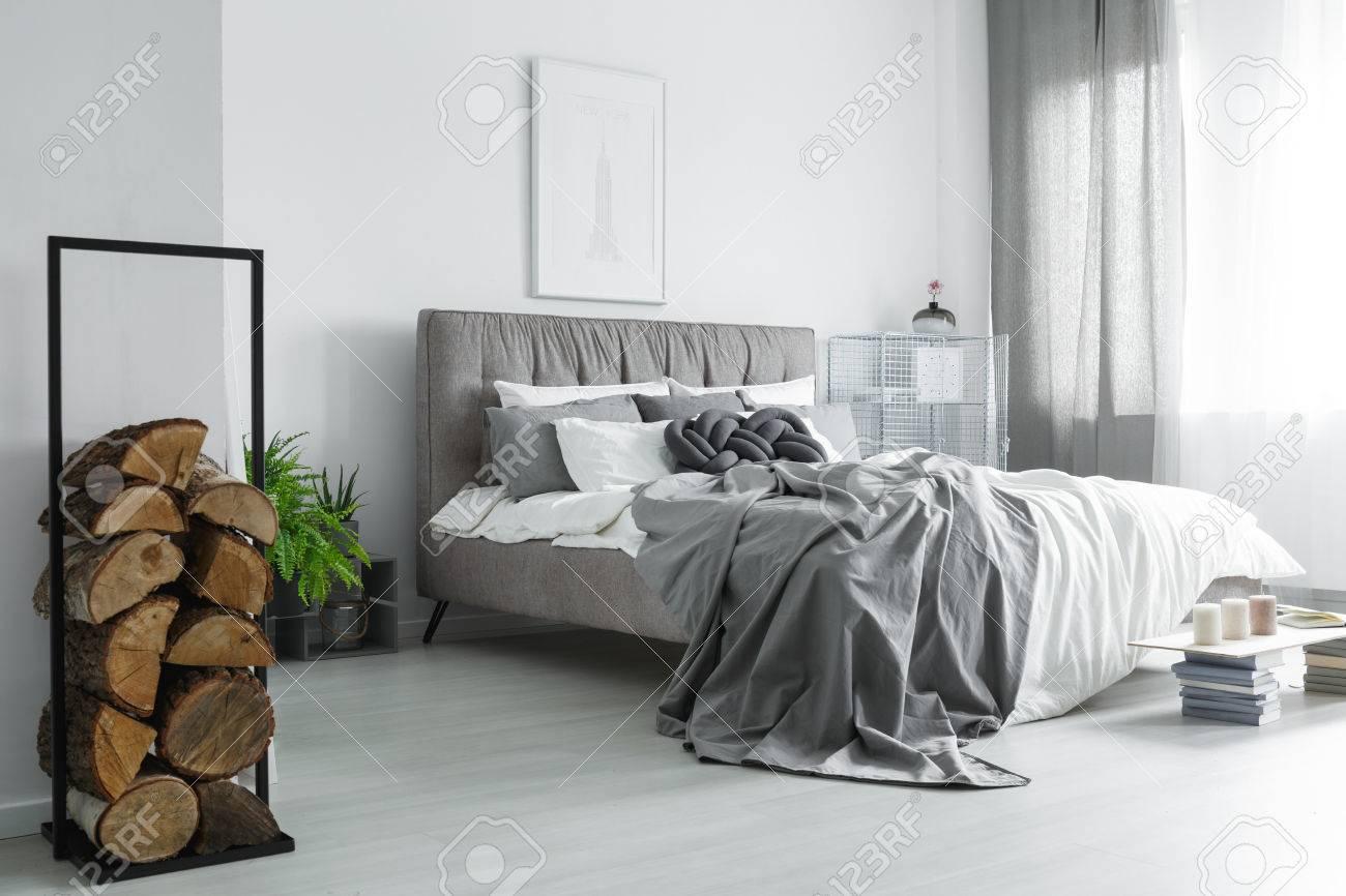 Acogedor Dormitorio Con Piezas De Leña Apiladas En Marco De Metal ...