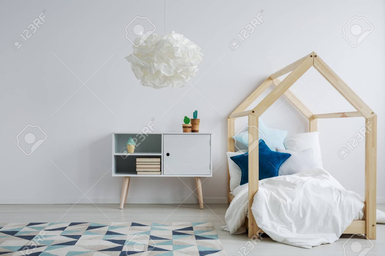 Elegant scandi style kid s room with a modern wooden bed next