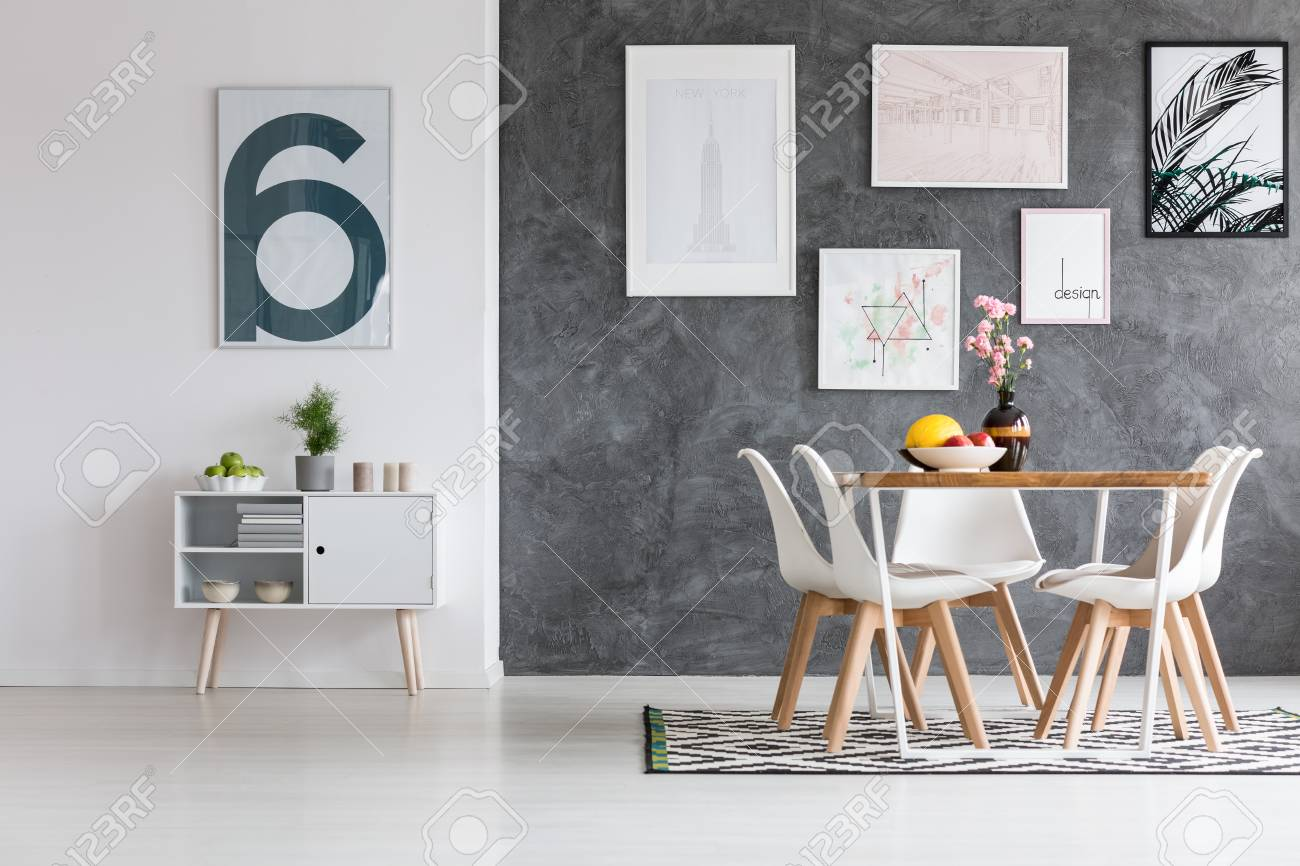 Amplio comedor con carteles en la pared oscura de hormigón y alfombra  estampada en piso blanco brillante