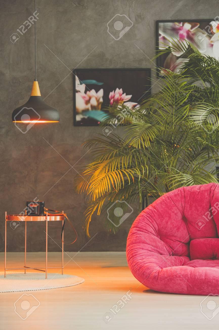 Chambre vintage avec une lumière sur une table basse et un fauteuil rose