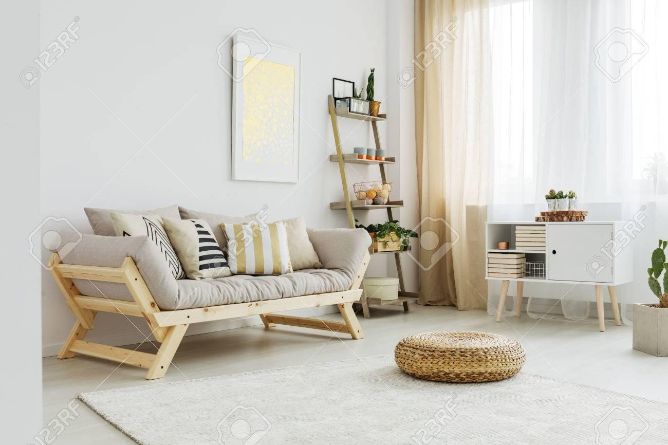 Material Puff Auf Weissem Teppich Vor Grauem Sofa Mit Gemusterten